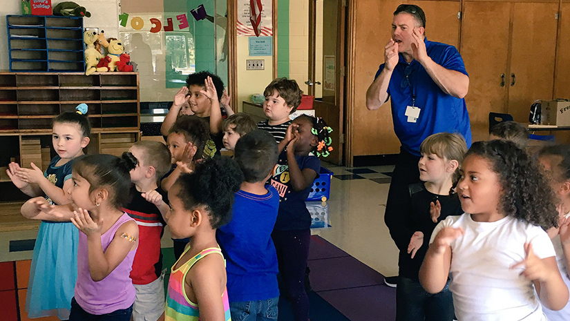 elementary students dancing in class with their teacher in a blue shirt dancing too