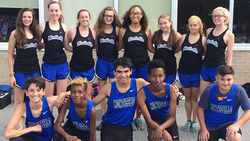 Eight Monticello high school girls and five boys all in their track uniforms, pose with a school in the background.
