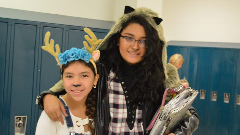 One female student wearing a headband with antlers and blue flowers smiles and poses with a teacher with animal ears on. during Spirit week