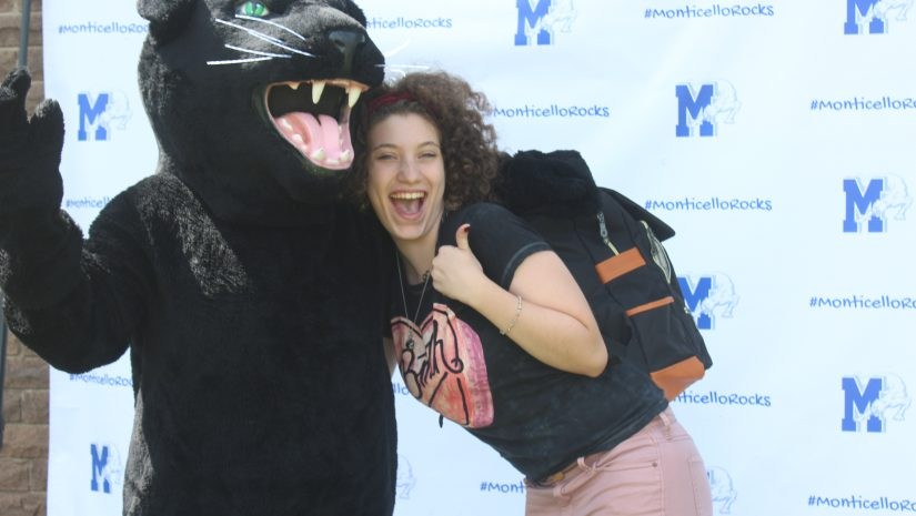 A female high school student in black t shirt and a backpack poses with panther mascot
