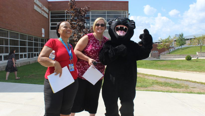 Two teachers, both in red shirts, smile with Monti the Panther in front of RJK Middle School on the first day of school.