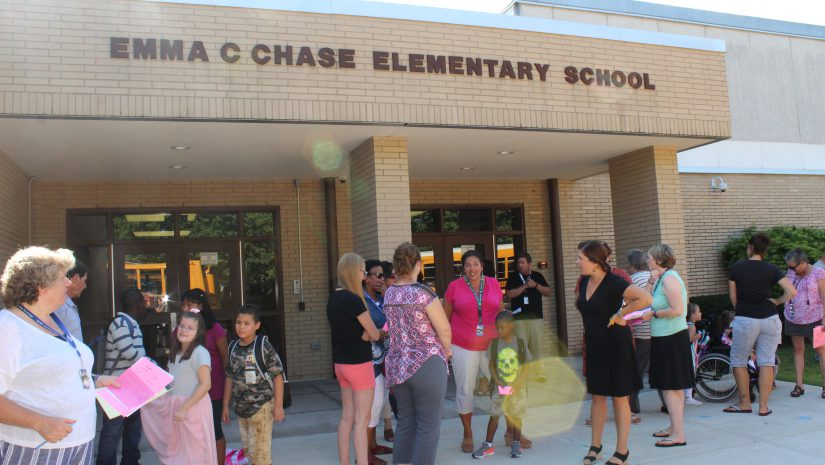 chase staff and students mingle outside the school with Emma C Chase Elementary School spelled out on the bricks in the front of the school
