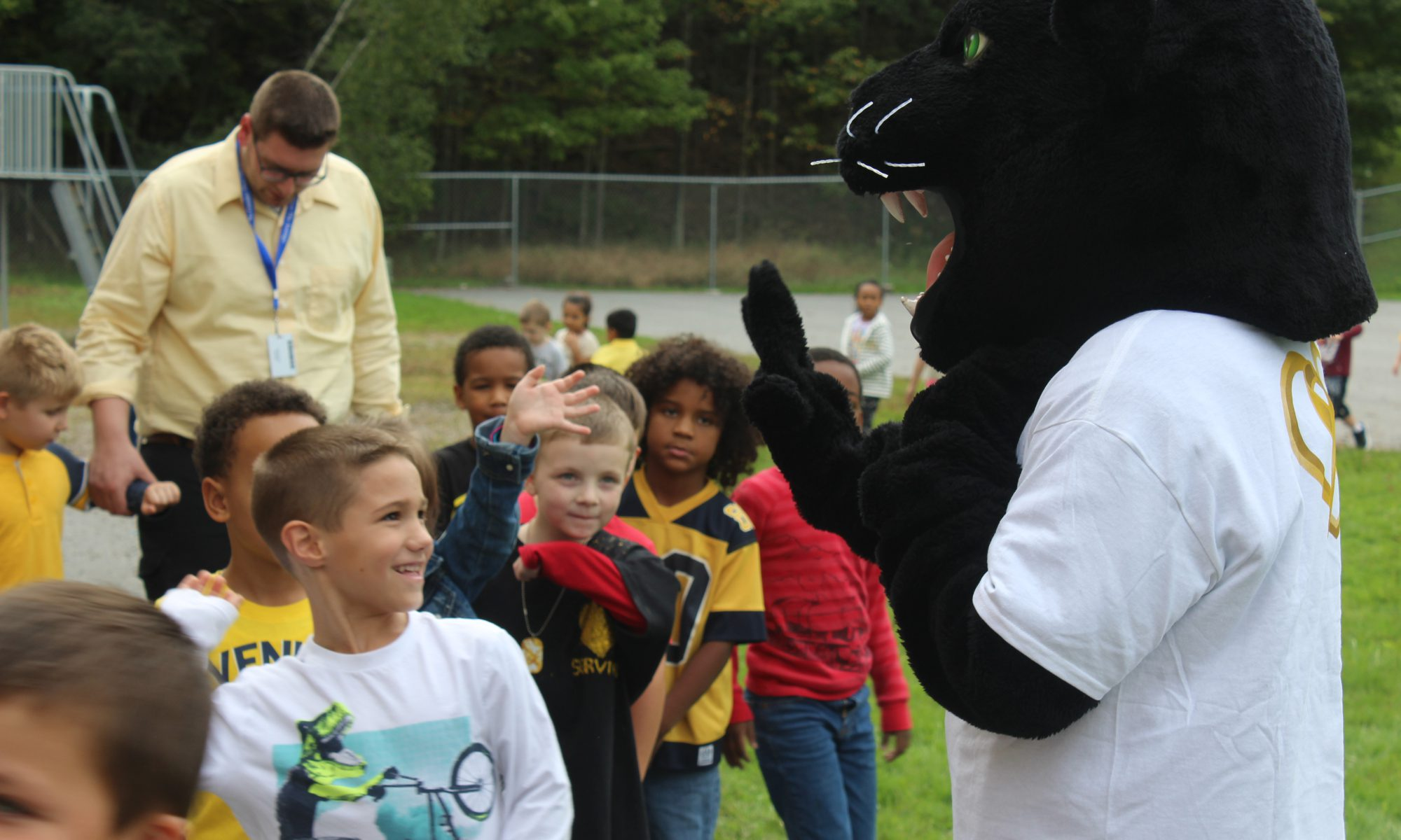Group of elementary students gather around Monti the Panther smiling and saving to him