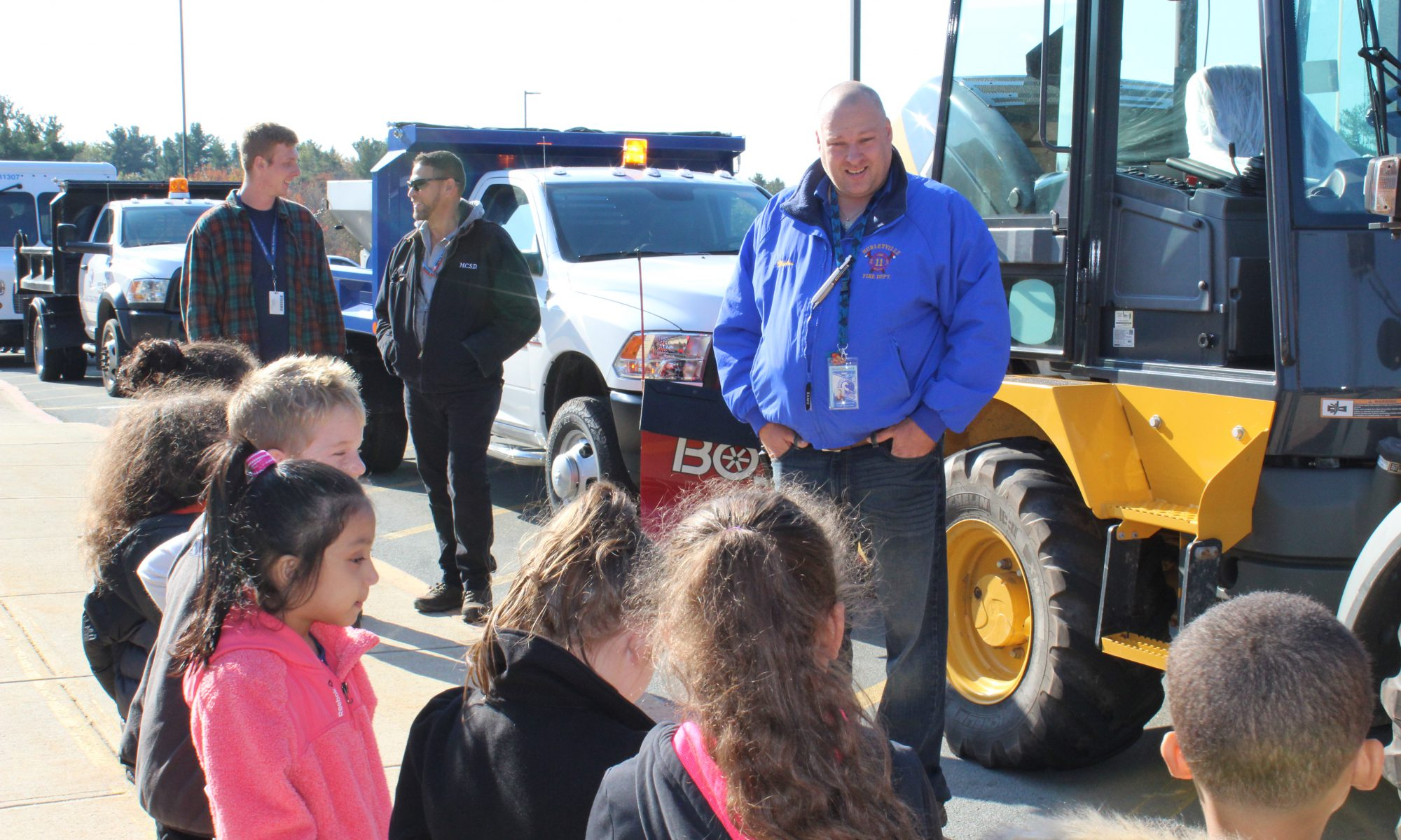 A man in a blue winter jacket speaks to a group of elementary students about facilities. There are many different trucks behind him.
