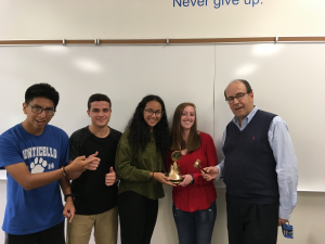 Four Monticello High School students receive their new gavel from a man in glasses, blue shirt and blue vest.