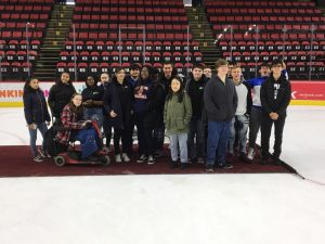17 high school students stand on a carpet on the ice in an arena