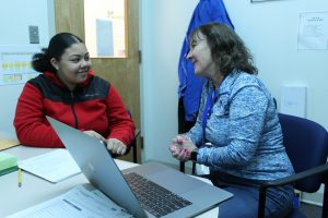 Eighth-grade student TyLia Huise sits with Guidance Counselor Karen Warden at a desk with a computer.