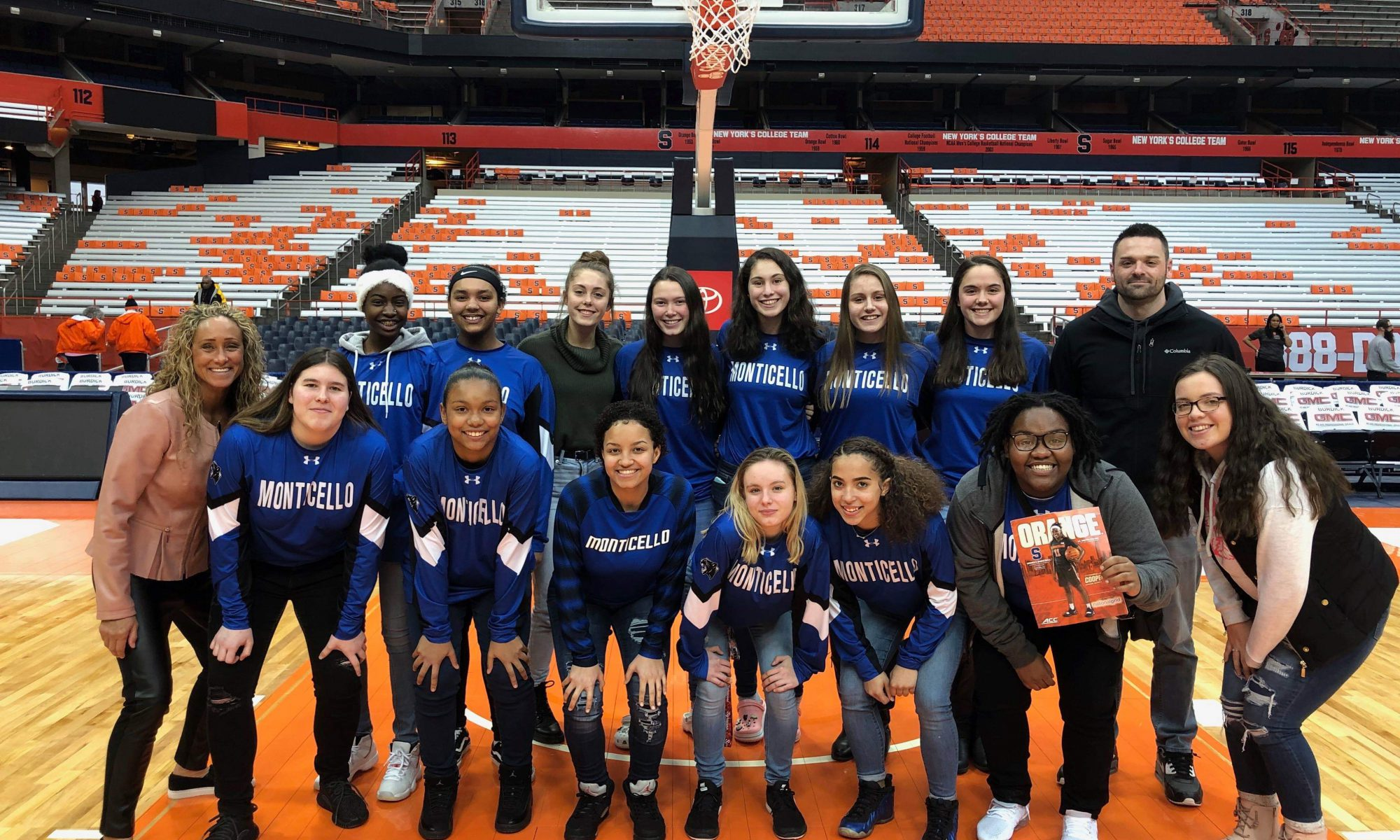 The Monticello High School girls basketball team stands center court at Syracuse