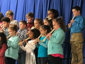 Group of elementary students on stage with blue curtain behind them play their recorders