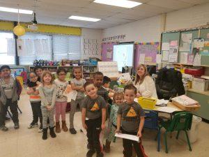 Kindergarten teacher Jennifer Somers sits at her desk surrounded by students