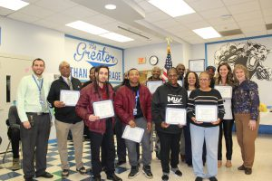 Member of the My Brother's Keeper team pose, holding their Board Award certificates