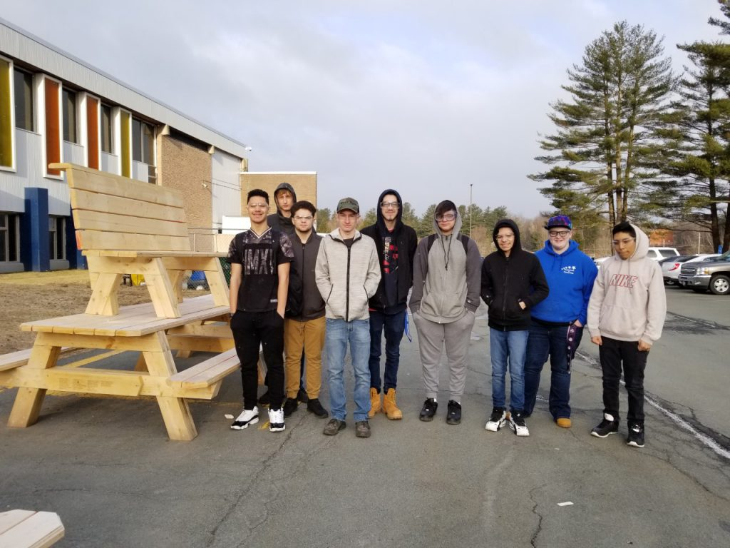Nine high school boys stand next to a wooden bench and a picnic table they made in class.