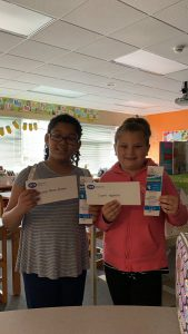 the two winning fourth grade students stand holding certificates