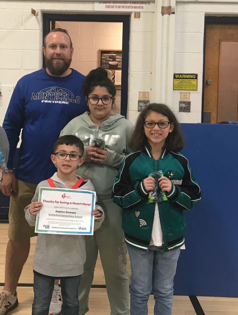 Man in blue shirt stands with three elementary students holding awards