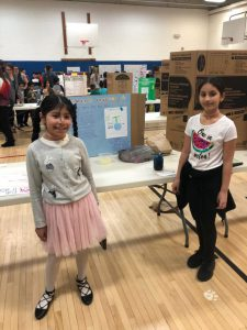 Two girls stand on either side of their science project