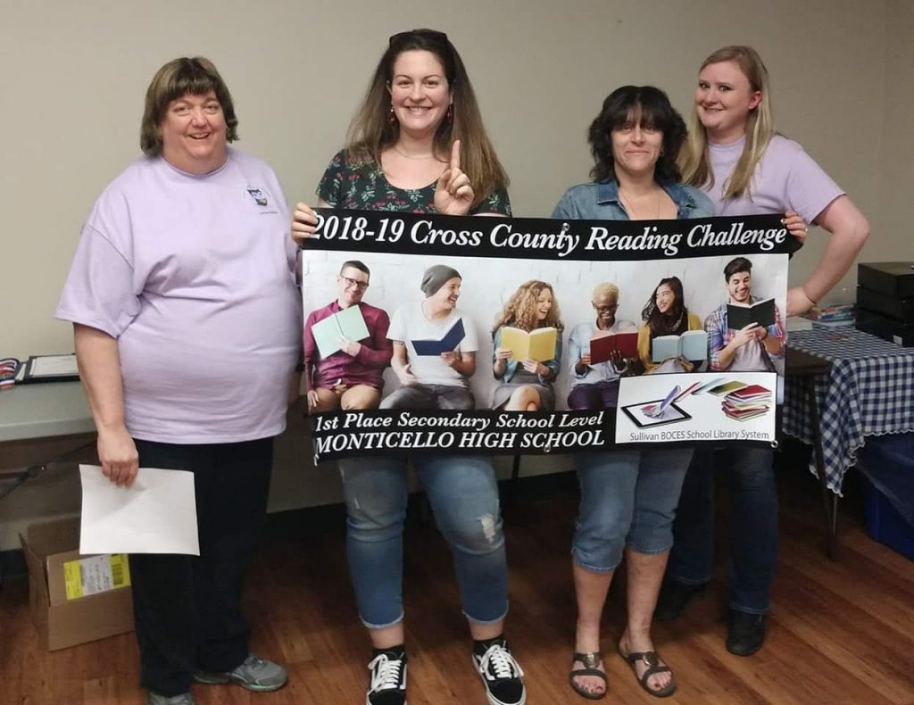 Four women, two holding a banner, declaring Monticello High School as the first place winner for secondary schools in reading in Sullivan County.