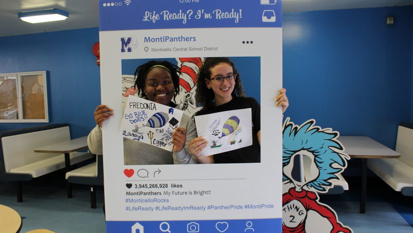 Two Monticello students post holding illustrations