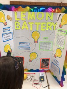 Poster board showing the words Lemon Battery in bright yellow with drawings of light bulbs all around and the experiment written out. A girl is reading it.