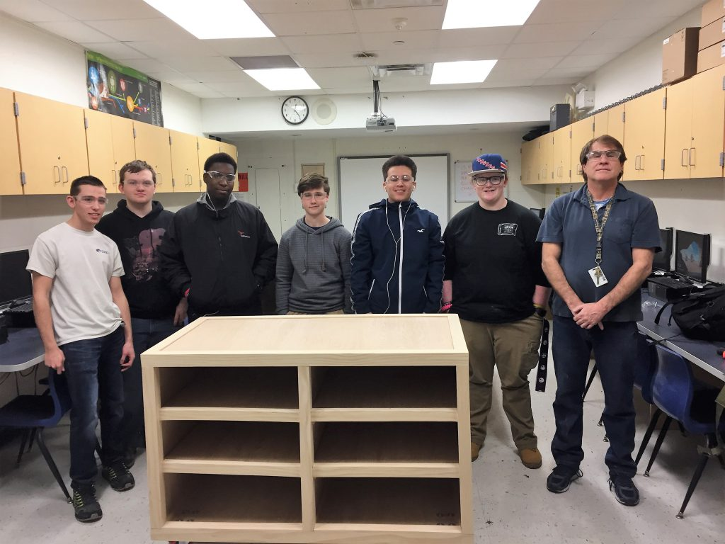 Five male students, all wearing goggles, and their teacher stand around the wooden store counter they built