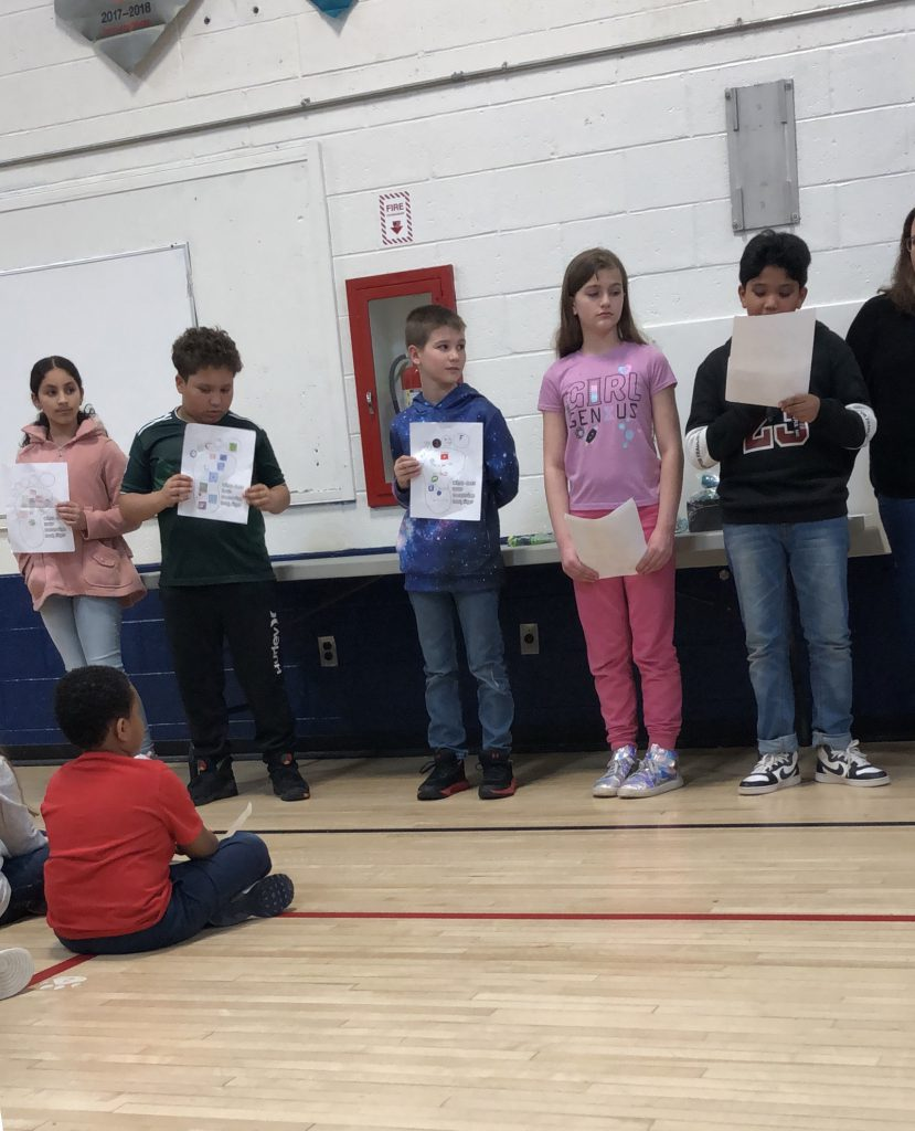 A line of elementary students hold their awards