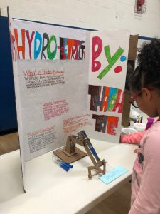 A colorful poster shows the hydro electricity experiment while a girl in a pink shirt reads it.