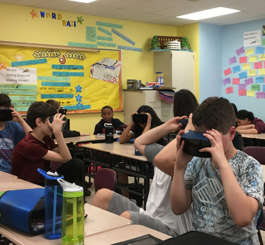 Several members of a middle school class holding virtual reality goggles to their eyes
