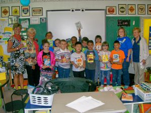 Students in Ms. Shopes class stand together smiling and holding books