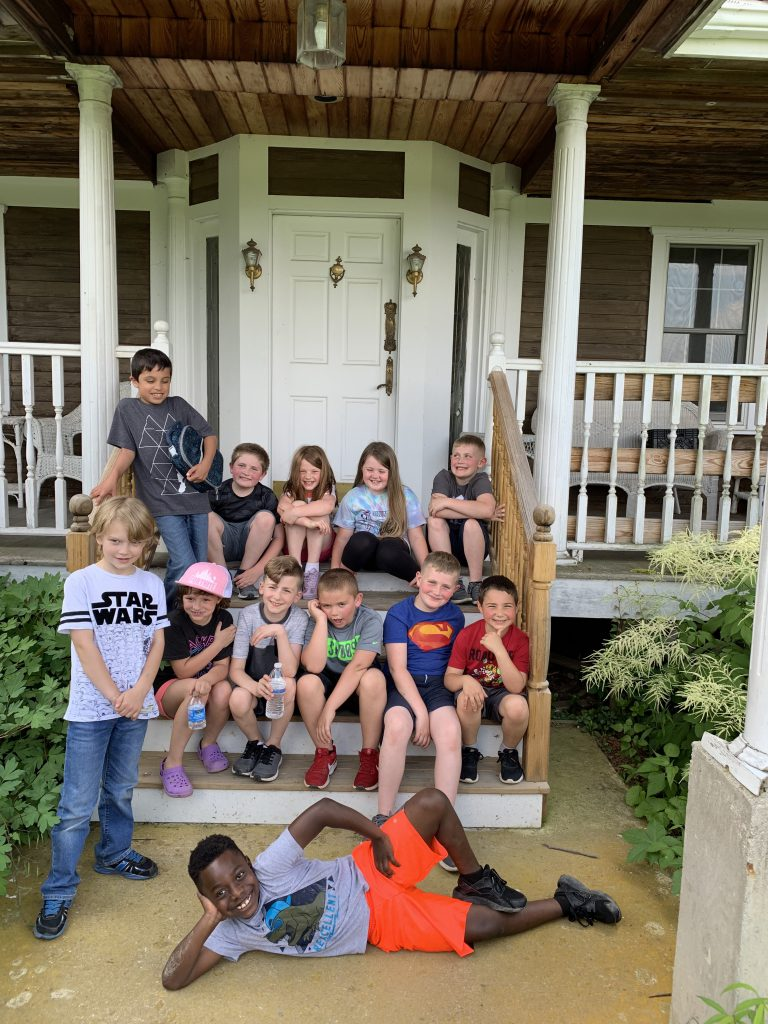 Twelve second grade students sit on the steps of a porch with one student lying across the front