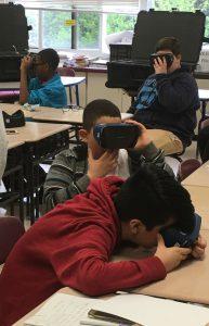 Three students looking through virtual reality goggles