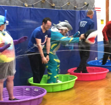 Five teachers stand in brightly colored wading pools as they are being squirted.