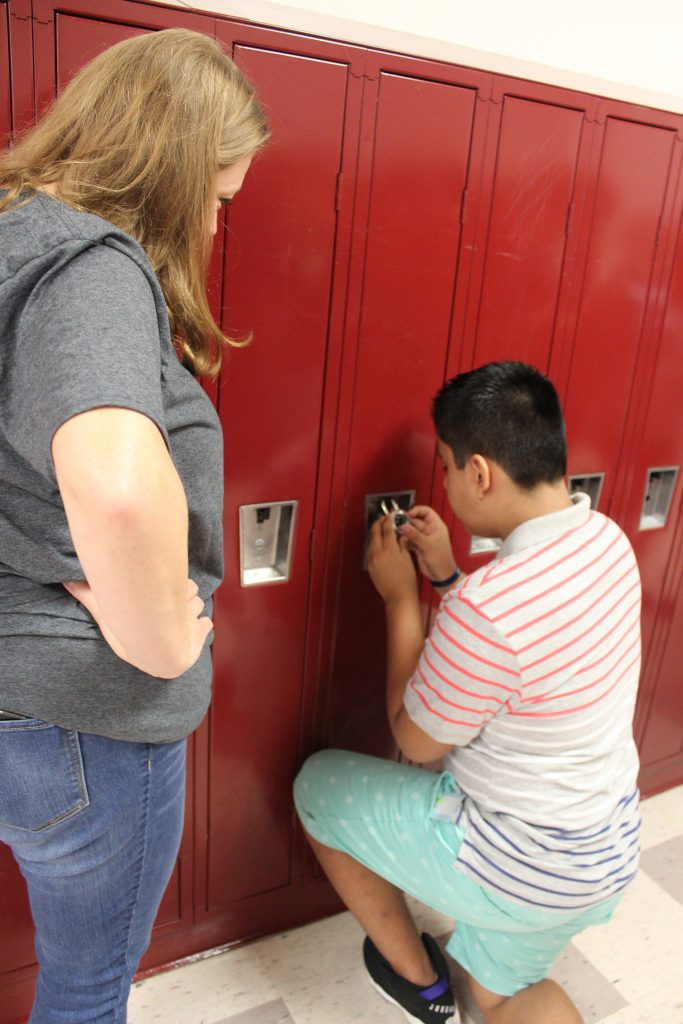 A student kneels at his locker, which is red, and tries the combination. A staff member stands by watching