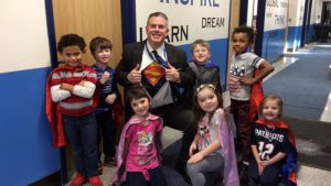 Assistant Principal Doug Murphy is surrounded by children in a hallway