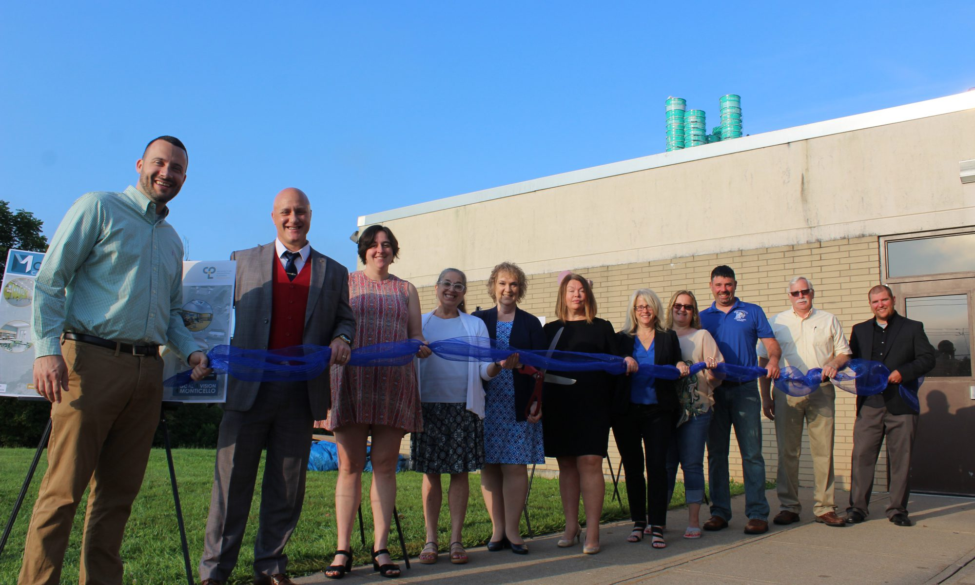 members of the board and representatives from the district's architectural firm cut a ribbon