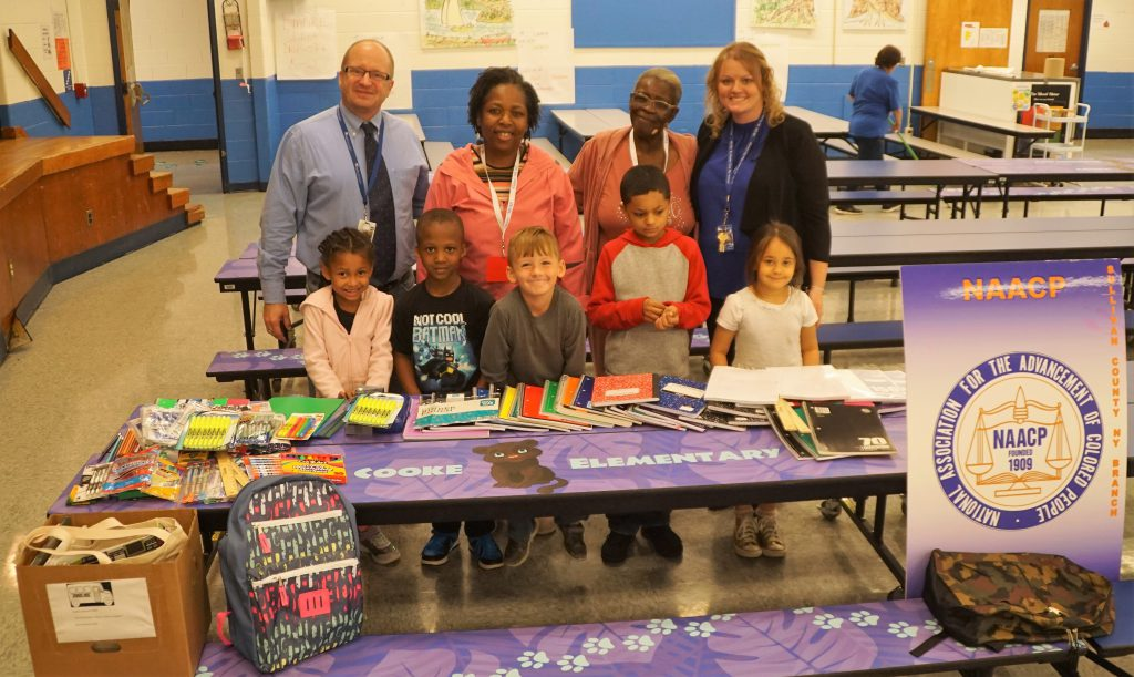 Four adults stand behind five elementary students. In front of them is a table with many school supplies
