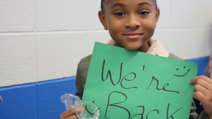 "Girl smiles and holds a green sign saying ""We're back"" on the first day of school"