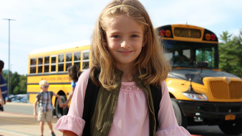 Smiling girl wearing a pink shirt. school bus in the background