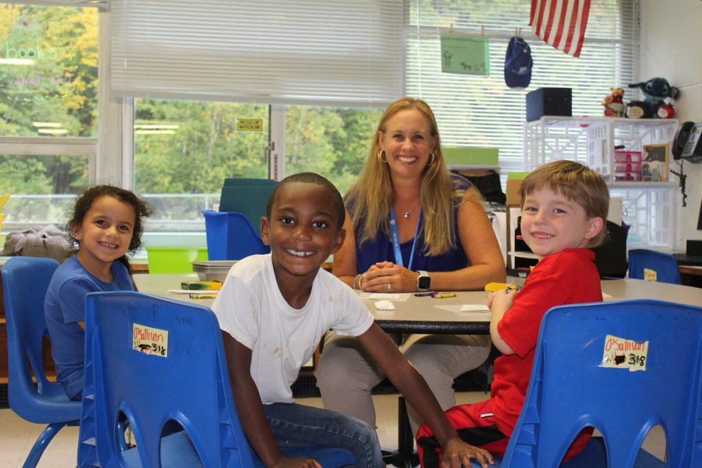 School Counselor Molly Messina sits at a table surrounded by three students