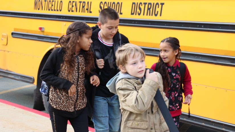 Four elementary school students walk past the school bus on their way to school