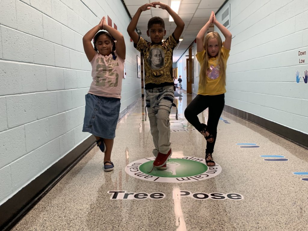 three students are standing in the yoga tree pose
