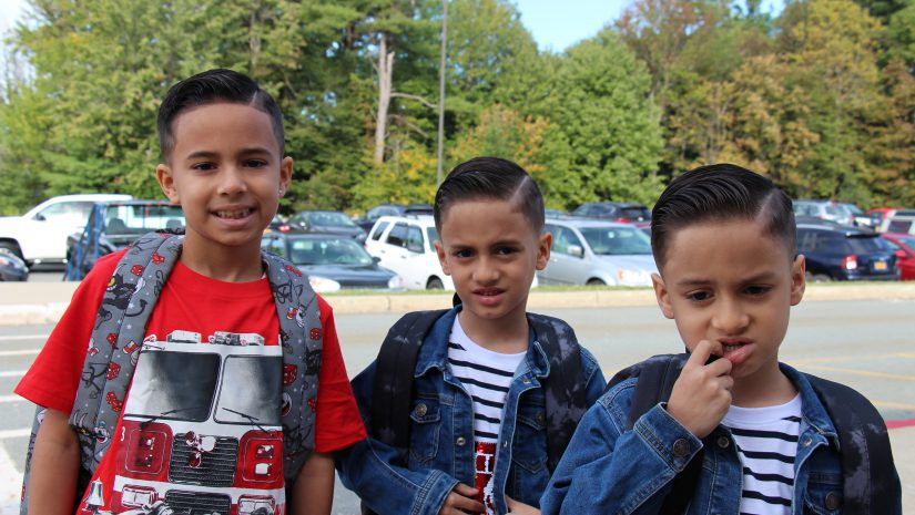 Three elementary school boys on the first day of school. two wearing denim jackets one with a red t shirt