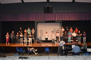 students performing in RJK's musical on stage during dress rehearsal