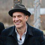 A man wearing a hat smiles. He has a dark winter jacket and an open-neck collards shirt