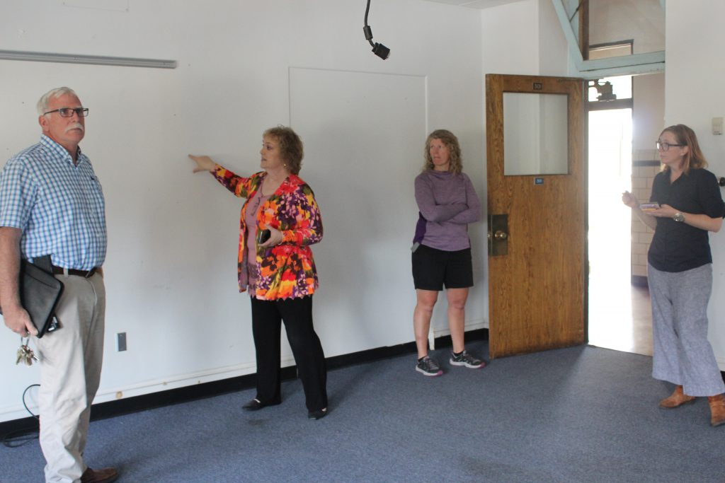 Board President Lori Orestano-James points to a wall while three other people look on