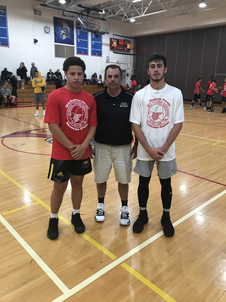 Coach stands in center of two high school basketball players