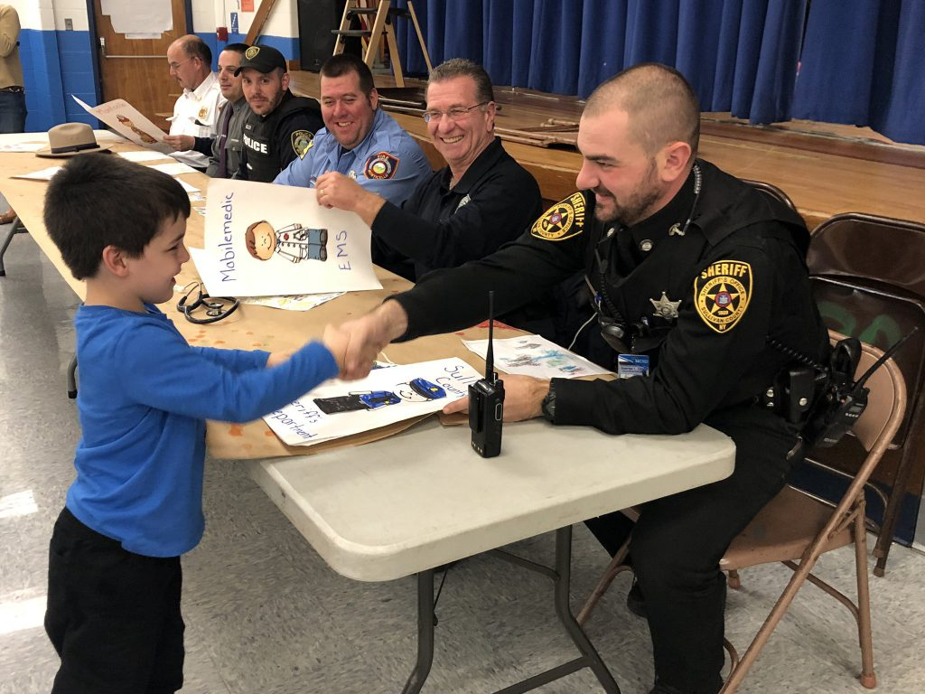 a police officer shakes the hand of a student during the community lunch
