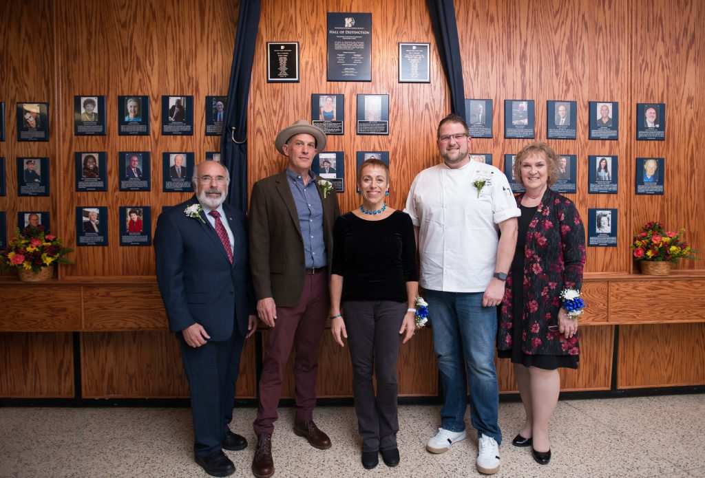 Five adults stand in front of a wall of wood with numerous plaques hanging on it.