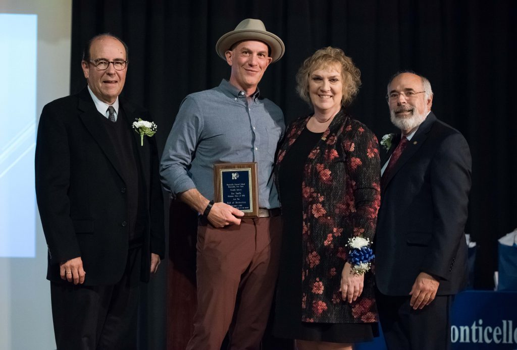 Four adults - three men and one woman - stand together. The man second from left is holding a small plaque he just received. He is wearing a gray hat.