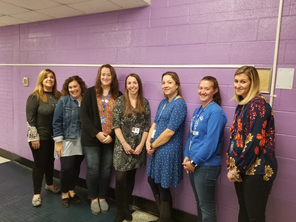 the kindergarten teachers at Cooke Elementary School are standing in a hallway and smiling