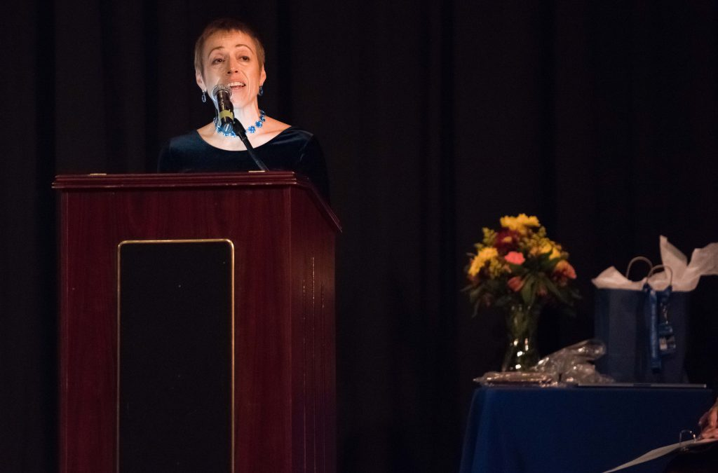 A woman stands at a podium speaking. Next to her is a table with gift bags and a vase filled with autumn flowers.