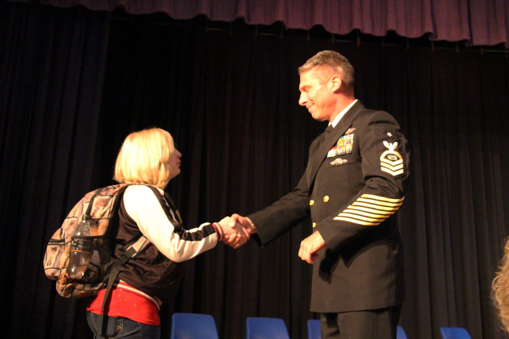 A high school student with blonde hair shakes the hand of a man wearing a uniform.